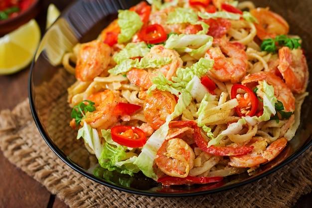 Pâtes udon aux crevettes, tomates et paprika.