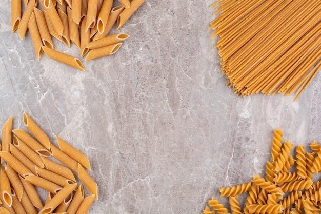 Pâtes variées de blé entier, sur le marbre.