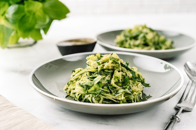 Pâtes végétaliennes de courgettes sur fond blanc. nourriture saine végétarienne