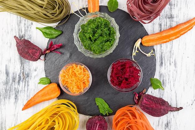 Pâtes végétariennes aux légumes crus colorés avec betteraves, carottes et épinards. ingrédient pour préparer.