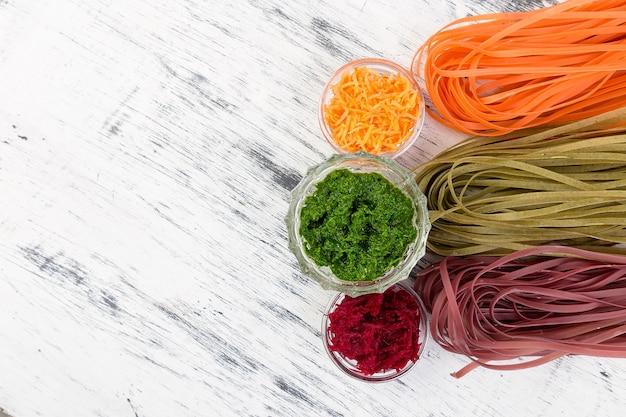 Pâtes végétariennes aux légumes crus colorés avec betteraves, carottes et épinards.