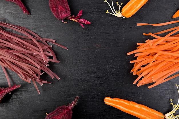 Pâtes végétariennes colorées aux légumes crus avec betteraves, carottes, appartement posé, espace de copie, vue de dessus, cadre,