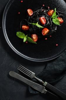 Pâtes végétariennes noires au basilic et aux tomates cerises.
