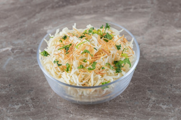 Pâtes vermicelles savoureuses aux légumes verts dans le bol, sur le marbre.