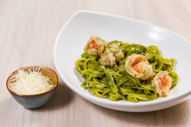 Pâtes vertes aux crevettes et au fromage en plaque blanche sur une table en bois clair dans un restaurant