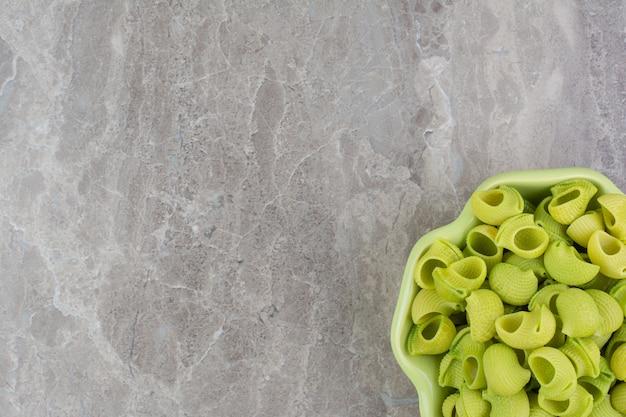 Pâtes vertes faites maison dans des assiettes sur l'espace gris.