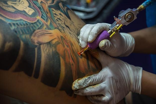 Pathumthani, thaïlande - 6 mai 2017: tatoueur professionnel non identifié dessin art sur le corps à