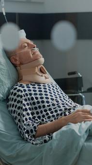 Patient âgé en convalescence après une intervention chirurgicale dans un lit d'hôpital