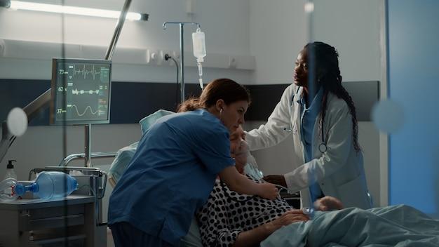 Patient âgé respirant lourdement dans un lit d'hôpital avec sac d'égouttement intraveineux personnel médical multiethnique h ...