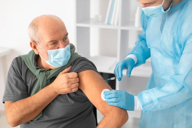 Un patient âgé se fait vacciner contre le coronavirus