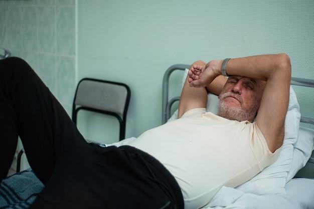 Patient âgé se reposant sur le lit à l'hôpital