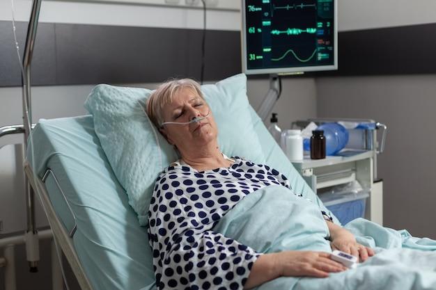 Patient âgé suite à un traitement de récupération portant dans un lit d'hôpital