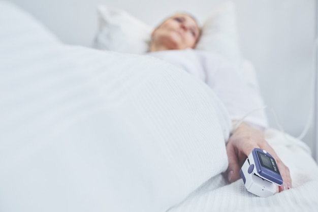 Patient allongé dans un lit d'hôpital et mesurant son pouls