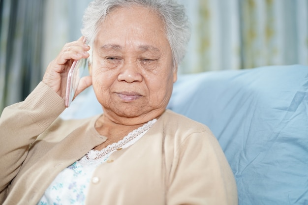 Patient asiatique senior femme parlant au téléphone mobile à l'hôpital.