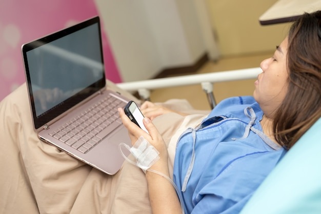 Patient de l'asie travaillant avec ordinateur portable pendant l'hospitalisation