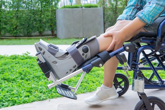 Patient assis sur un fauteuil roulant une personne portant une chaussure conçue spécifiquement pour la cheville ou