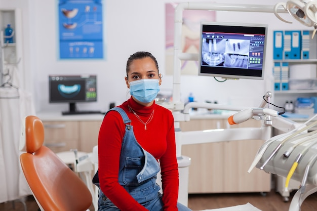 Patient ayant des problèmes d'hygiène dentaire portant un masque facial dans une clinique de détail regardant la caméra. femme en cabinet de stomatologie assise sur une chaise en attente d'un médecin pour une expertise professionnelle.