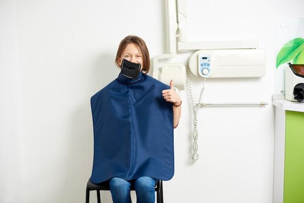 Patient d'un cabinet dentaire avec un kofferdam est préparé pour une radiographie et sourit à la caméra alors qu'il est assis sur la chaise dans une salle blanche