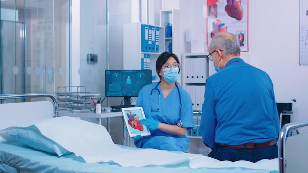 Un patient cardiaque reçoit des explications d'une infirmière portant un masque dans une clinique hospitalière privée moderne. rachitisme, ostéomalacie, ostéogenèse imparfaite ou consultation de maladie des os de marbre pendant le coronavirus