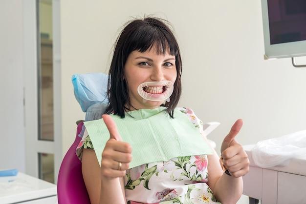 Patient dans la chaise de dentiste montrant les pouces vers le haut