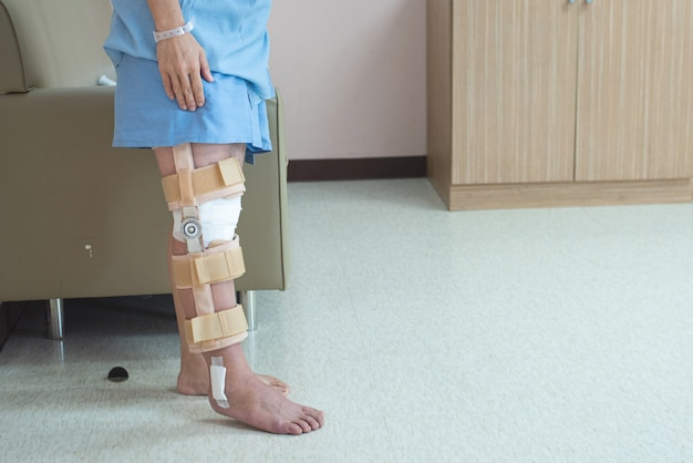 Patient debout avec le soutien de l'orthèse du genou et du plâtre après la chirurgie du genou ligamentaire pcl à l'hôpital orthopédique, concept de récupération et de soins de santé.