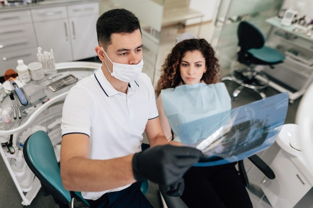 Patient et dentiste examinant la radiographie