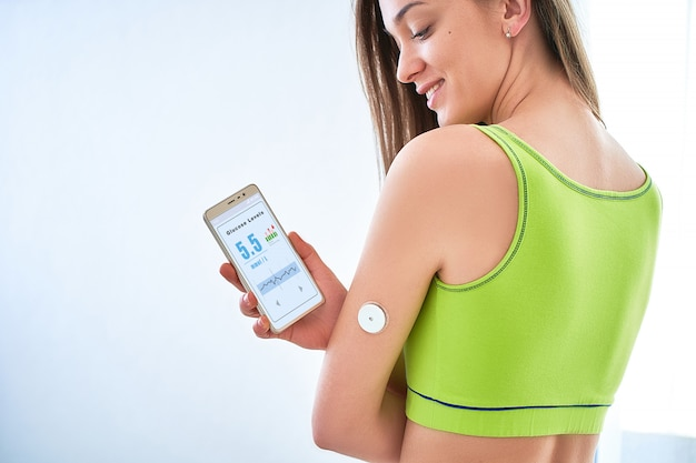 Patient diabétique vérifiant le niveau de glucose avec un capteur à distance et un smartphone.