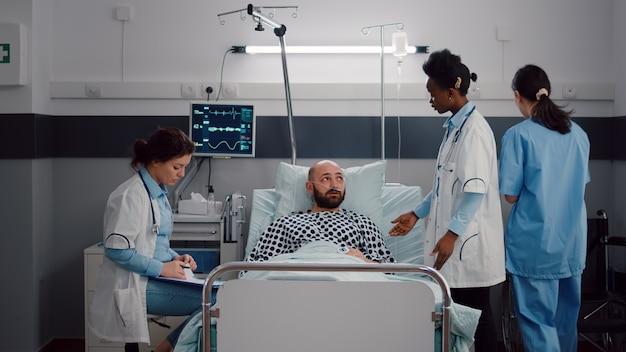 Patient discutant avec des médecins tout en se reposant au lit pendant la convalescence médicale