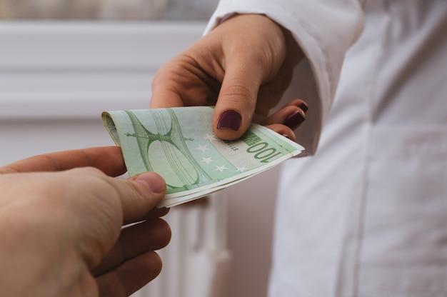 Patient donne de l'argent à un médecin à l'hôpital,