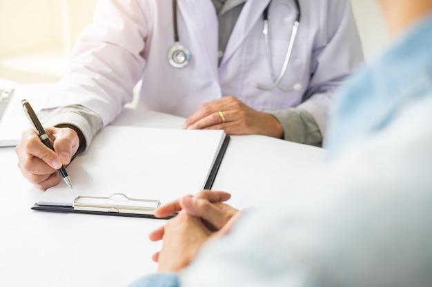 Patient écoutant attentivement un médecin masculin expliquant les symptômes du patient ou posant une question alors qu'ils discutent de la paperasserie ensemble dans une consultation