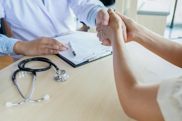 Le patient écoute attentivement un médecin masculin expliquant les symptômes du patient ou posant une question alors qu'ils discutent de la paperasserie ensemble dans une consultation