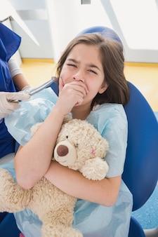 Patient effrayé couvrant la bouche et tenant un ours en peluche