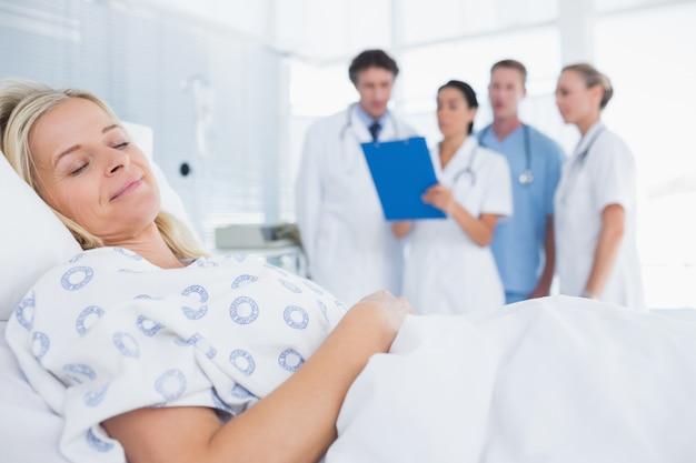 Patient endormi avec des médecins derrière