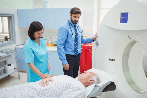 Un patient est chargé dans une machine irm pendant que le médecin et le technicien regardent