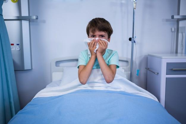 Patient éternuant son nez en salle