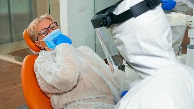 Patient expliquant le problème dentaire au stomatologue portant une combinaison de protection pendant la pandémie mondiale. assistant et médecin avec des gants de masque de protection faciale examinant une femme depuis une chaise stomatologique