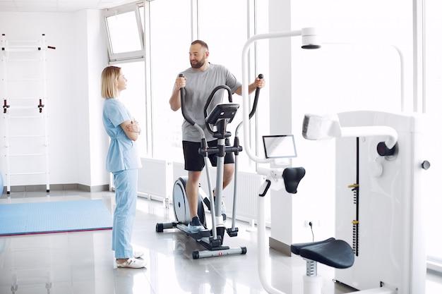 Patient faisant de l'exercice sur spin bike dans une salle de sport avec thérapeute
