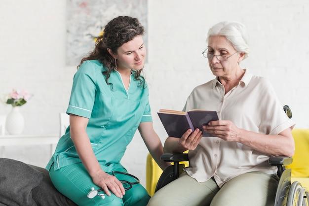 Patient féminin senior handicapé assis sur une chaise roulante, lecture de livre avec infirmière