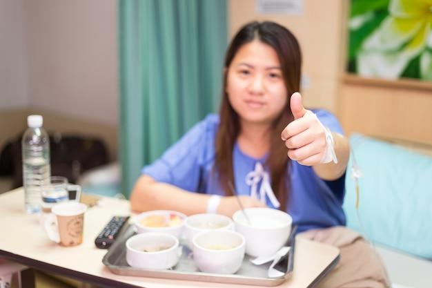 Patient femme asiatique pouce en l'air signe ok et sourire tout en se reposant sur le lit d'hôpital, conc