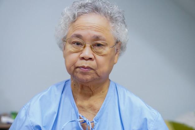 Patient de femme senior asiatique assis sur le lit à l'hôpital.