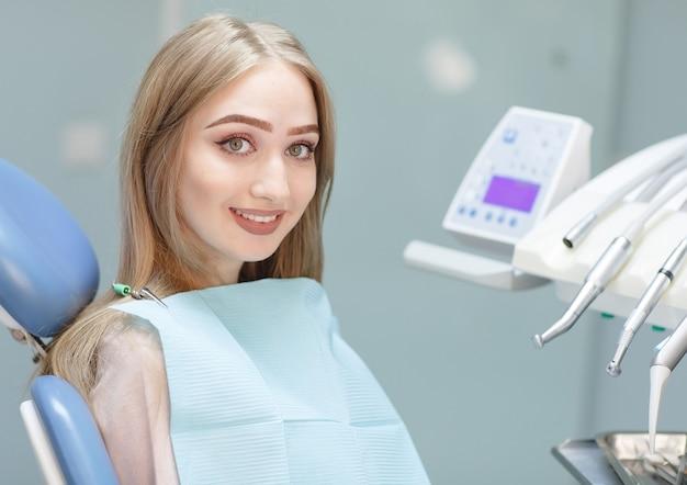 Un patient heureux dans une clinique dentaire est assis sur une chaise.