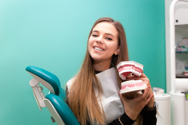 Patient heureux montrer l'hygiène des dents sur le modèle de mâchoire. femme au bureau de stomatologie clinique. concept de soins dentaires