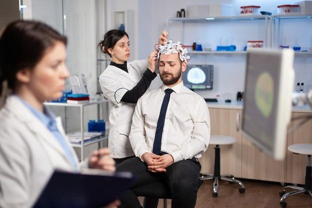 Patient homme visitant un chercheur médical professionnel en médecine neurologique testant les fonctions cérébrales avec un casque eeg. médecin surveillant le système nerveux, découvrant le diagnostic de la maladie.