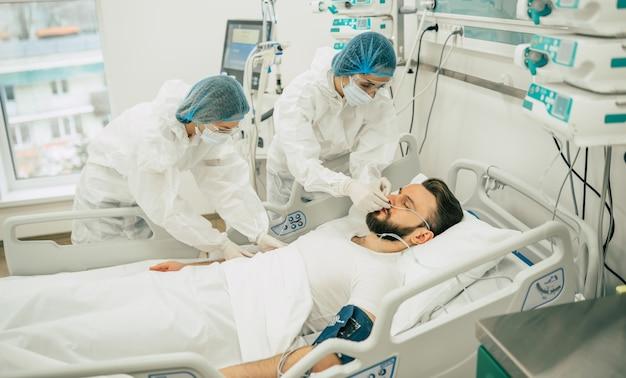 Patient infecté par le coronavirus covid-19 dans une salle de quarantaine de l'hôpital avec des médecins en tenue de protection pendant qu'ils le soignent