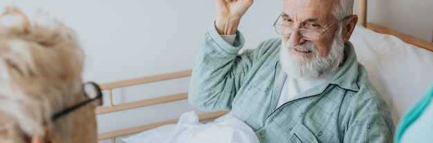 Patient malade plus âgé allongé dans un lit dans une maison de soins infirmiers