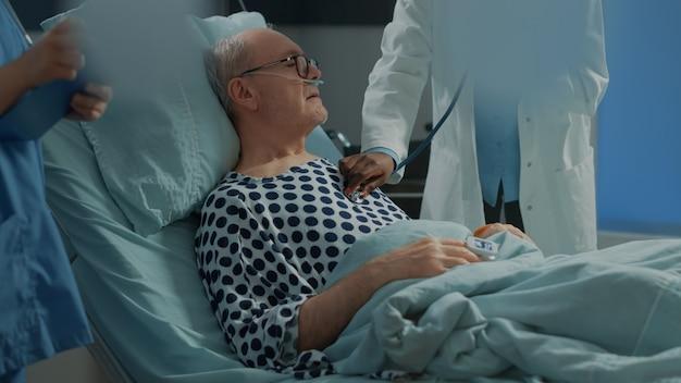 Un patient malade reçoit une consultation d'un médecin afro-américain à l'aide d'un stéthoscope dans une salle d'hôpital à...
