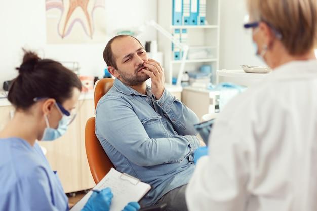 Patient malade souffrant de maux de dents parlant avec un stomatologue montrant la masse affectée