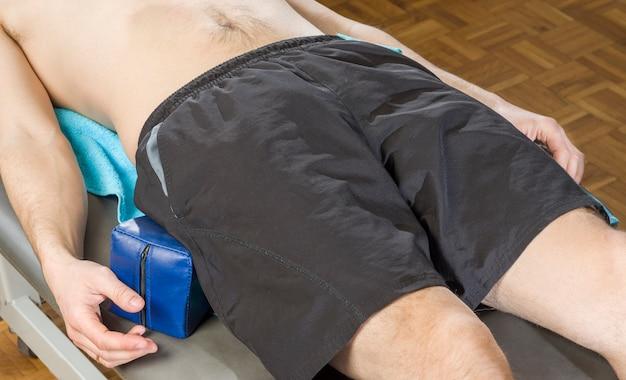Patient masculin sur une civière avec des cales pour la protection posturale du sacro-iliaque.