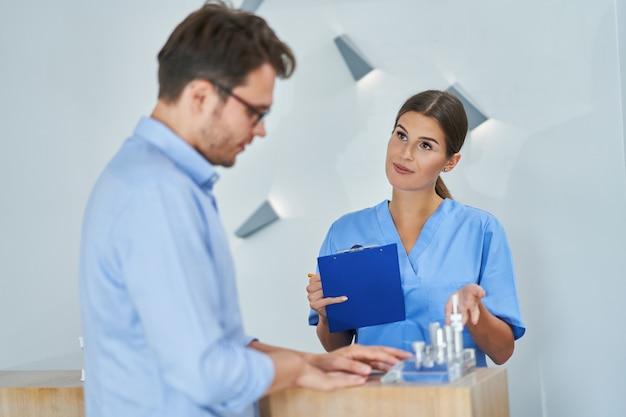Patient masculin signant des documents dans une clinique dentaire