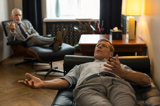 Patient masculin tendu allongé sur le canapé devant son psychothérapeute tout en se plaignant de ses problèmes